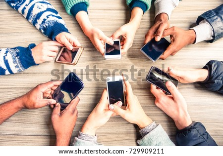 Hands circle using phones on table top view - Multiracial people holding mobile devices sitting around at office desk - Concept of friends team working and modern communication technology above image