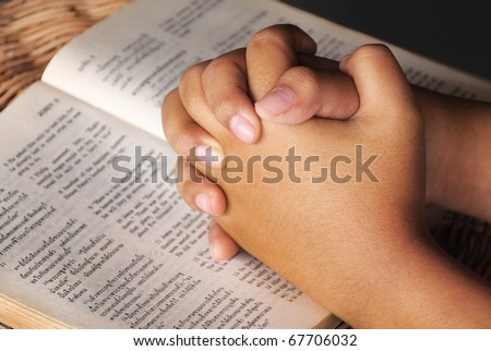Hands clasped in prayer on Holy Bible