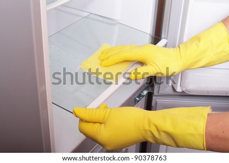 Hands cleaning refrigerator. #90378763
