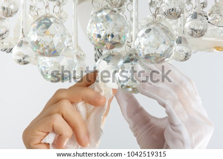 hands cleaning the chandelier with rag, close up