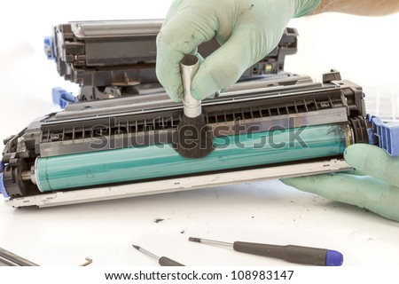 hands cleaning toner cartridge with brush the dust. worker Laser printer on a workbench. Printer workshop
