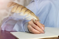 Hands close up. A woman with a French manicure in a blue shirt writes with a feather in a notebook. Business woman  making notes on paper.