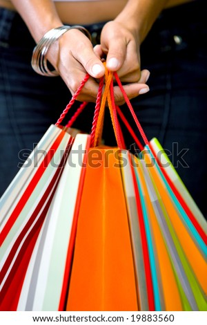 hands close up holding shopping bags in various colours