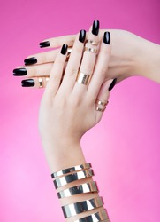 Hands close up of young woman with black manicure wearing gold bracelet and knuckle rings