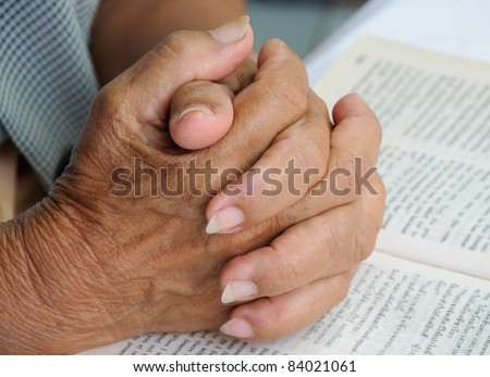 Hands closed praying on open bible