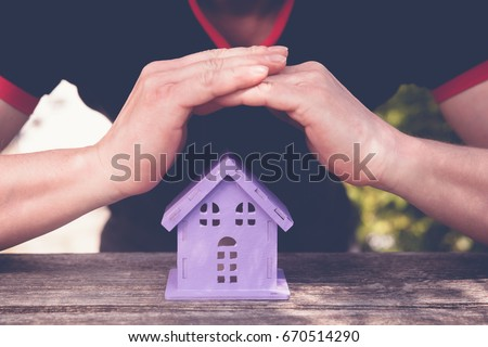 Hands closing toy house  of lavender color, as a symbol of safety #670514290