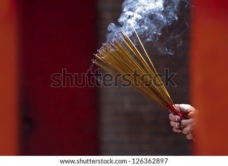 Hands clutching lit incense sticks in a Temple in Ho Chi Minh City, Vietnam.