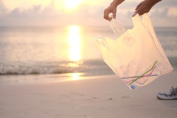 Hands collecting plastic in a white plastic bag on the beach.Pollute the ocean.Help to keep nature clean, garbage from the beach.Ecological problems.Environmental crisis.Coastal cleanup day concepts