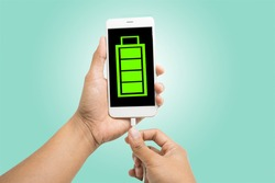 Hands connecting smartphone with low battery to a charger