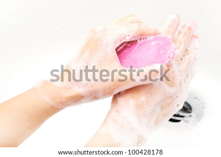 hands covered with soap being washed in the sink