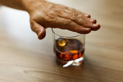 Hands covers with a palm a glass of whiskey To stop drinking. Alcoholism concept. Stop alcohol addiction. Addicting to alcoholic drink.