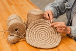 hands craftswoman knitting product from jute. Hobbies, needlework made from natural materials.