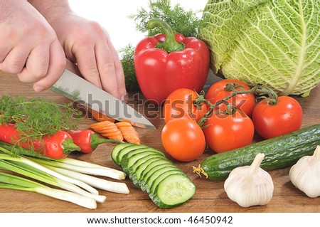 Hands cut a knife a carrot among vegetables on board