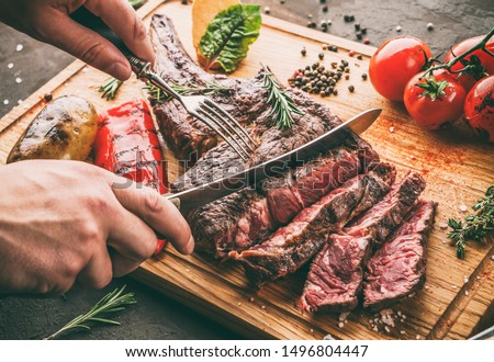 Hands cut grilled tomahawk meat medium rare or rib eye steak on wooden cutting board with grilled vegetables on dark background, close up, toning