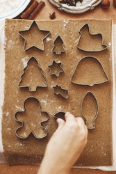 Hands cutting gingerbread dough with festive metal cutters on rustic table flat lay. Person making Christmas gingerbread cookies, holiday advent
