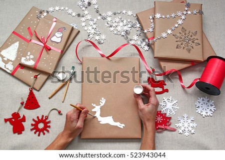 Hands decorating packed christmas gifts. Drawing a deer on brown ...