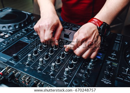 Hands DJ mixing music at the club during the event