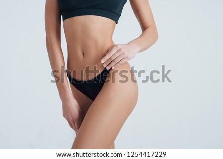 Hands down. Close view of beautiful slim woman body in black underwear in the studio.