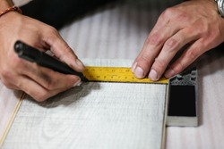 Hands draw marker on the ruler. Laying laminate. Close up.