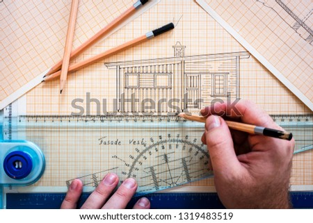 Hands drawing cabin on drawing board with ruler and pencils. Designer, architect, draw, lines, paper, work, working, at work concept.