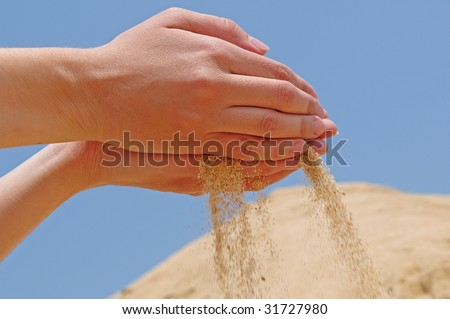 hands dropping sand against blue sky