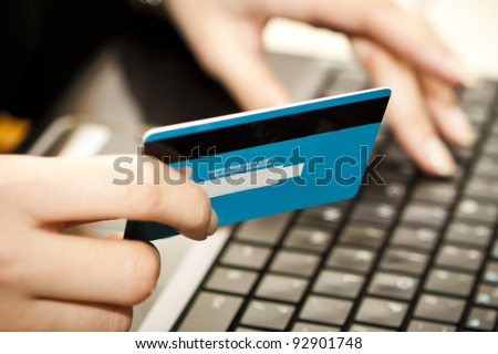 Hands entering credit card information into a laptop