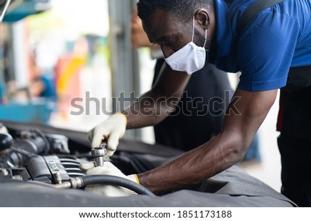 Hands Expertise car mechanic in auto repair service. Car maintenance and auto service garage concept. Black man wearing medical face mask protec virus corona