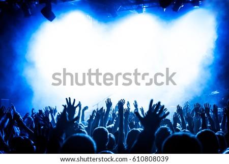 hands fans during a concert