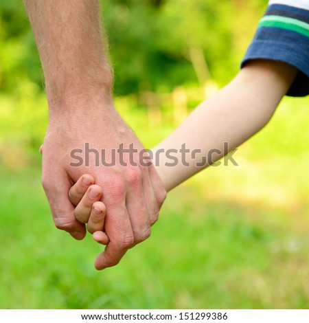 hands, father lead his child in summer garden nature outdoor, trust family concept