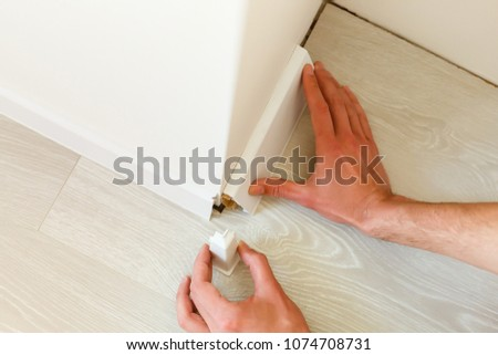 Hands fitting the baseboard to a bright wall