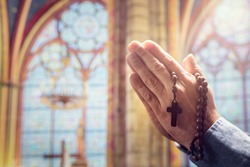 Hands folded in prayer in church with rosary beads and religious cross concept for faith, spirtuality and religion