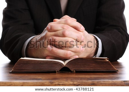 Hands folded in prayer on an open bible