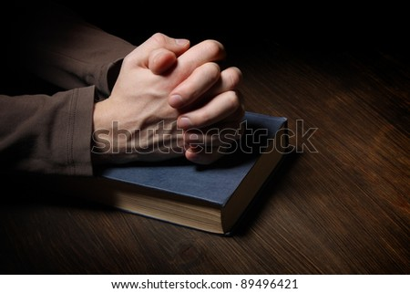 Hands folded in prayer over a Holy Bible