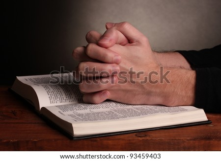 Hands folded in prayer over a Holy bible on wooden table on grey background #93459403