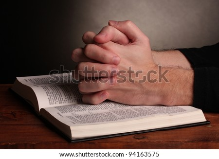 Hands folded in prayer over a Holy bible on wooden table on grey background #94163575