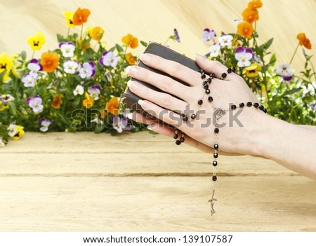Hands folded in prayer over old Holy Bible. Wooden background.
