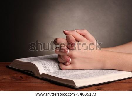 Hands folded in prayer over open russian Holy Bible on black background #94086193