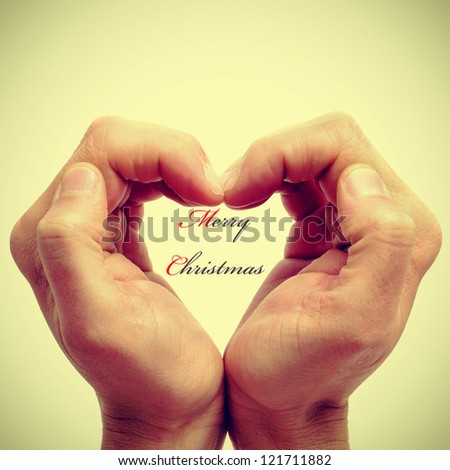 hands forming a heart and the sentence merry christmas written inside, with a retro effect - stock photo