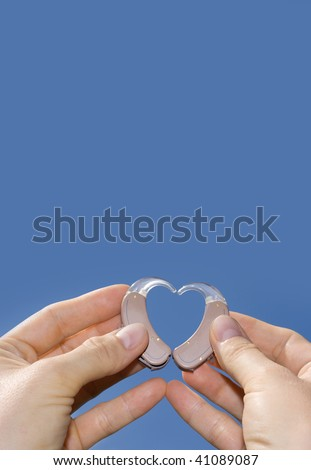 Hands forming a heart shape from digital hearing aids in front of a blue sky background useful for texts.