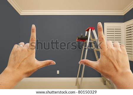 Hands Framing Grey Painted Room Wall Interior with Ladder, Paint Bucket and Rollers.
