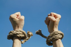 Hands free from shackles are stretched to the blue sky. Feeling of freedom