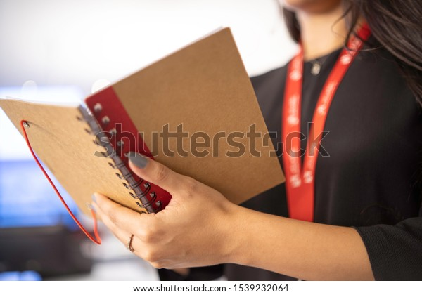 Stock photo of hands of a girl with an open notebook of recycled material and red details. Office work.