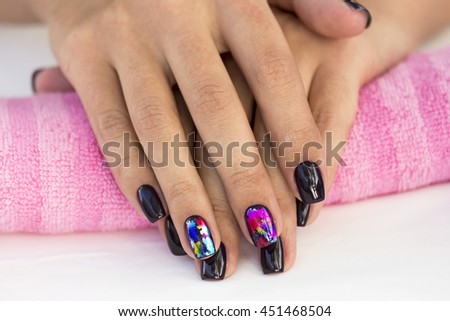 Hands girl with beautiful manicure on a pink towel. #451468504