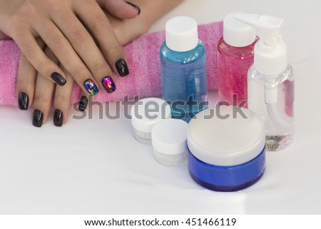 Hands girl with beautiful manicure on a pink towel with a set of Cosmetic jars