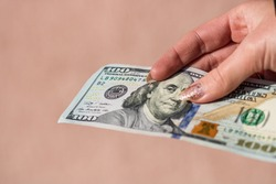 Hands giving money like a bribe or tips. Holding US dollars banknotes on a blurred background, US currency