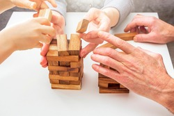 Hands grandmother, grandfather and grandson play board game with wooden blocks. Concept of family relationships, traditions and pastime. Development fine motor skills and spatial thinking