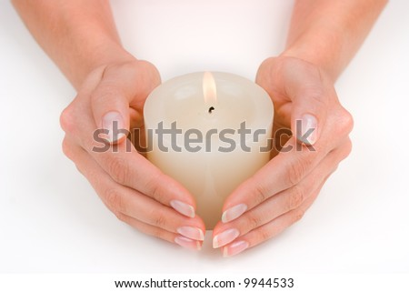 Hands guarding a white candle over white