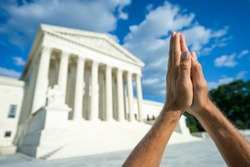 Hands held together in beseeching prayer standing in front of the US Supreme Court building in Washington DC