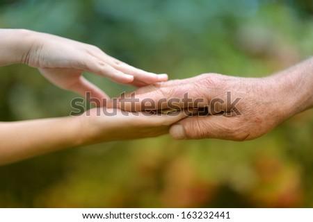 Hands held together on a natural dark background