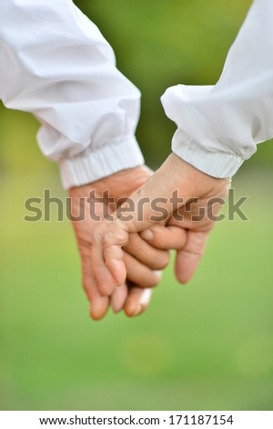 Hands held together on a natural green background